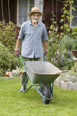 Senior with a barrow in the garden — Foto de Stock