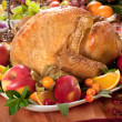 Roasted turkey on holiday decorated table - Stock Photo