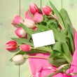 Bouquet of rose tulips with blank card — Stock Photo