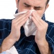 Stock Photo: Sick mblowing his nose