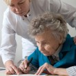 Stock Photo: Assisting senior womby nurse at home.