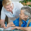 Assisting a senior woman by nurse at home. - Stock Photo
