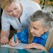 Assisting a senior woman by nurse at home. — Stock Photo
