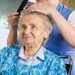 Stock Photo: Nurse dressing hair of senior woman