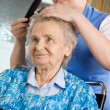 Nurse dressing the hair of a senior woman — Stock Photo #6867503