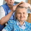 Nurse dressing the hair of a senior woman — Stock Photo