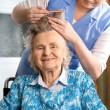 Nurse dressing the hair of a senior woman - Stock Photo