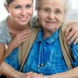 Stock Photo: Senior womwith her home caregiver