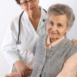 Health care worker helps  elderly woman - Stock Photo