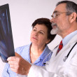 Doctor explaining x-ray results to patient — Stock Photo