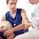 un equipo médico dando primeros auxilios al joven deportista — Foto de Stock
