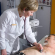 Doctor performing an EKG test - Stock Photo