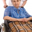 Young nurse encouraging senior  woman in wheelchair — Stock Photo