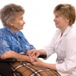Young nurse encouraging senior  woman in wheelchair - Stockfoto