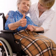 Health care worker and elderly woman in wheelchair — Stock Photo