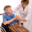 Young nurse encouraging senior woman in wheelchair — Stock Photo #6869061
