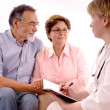 Senior couple visiting a doctor — Stock Photo