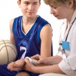 Doctor giving first aid to a young sportsman — Stock fotografie