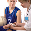 Doctor giving first aid to a young sportsman - Stock Photo