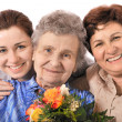 Great grandmother receiving a bunch of flowers - Stockfoto