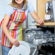 Woman loading dishes to the dishwasher — Stock Photo