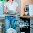 Woman loading dishes to the dishwasher — Stock Photo #6869646