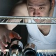 Fat man gets beer from the fridge - Stockfoto