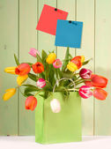Fresh tulips in shopping bag — Stock Photo