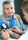 An elderly women being examined by a doctor — Stock Photo