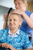 Enfermera vistiendo el cabello de una mujer senior — Foto de Stock