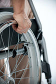 Hand of senior woman on wheelchair — Stock Photo