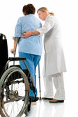 Nurse helps a senior woman on crutches — Stock Photo