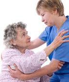 Nurse helps the senior woman get up — Stock Photo