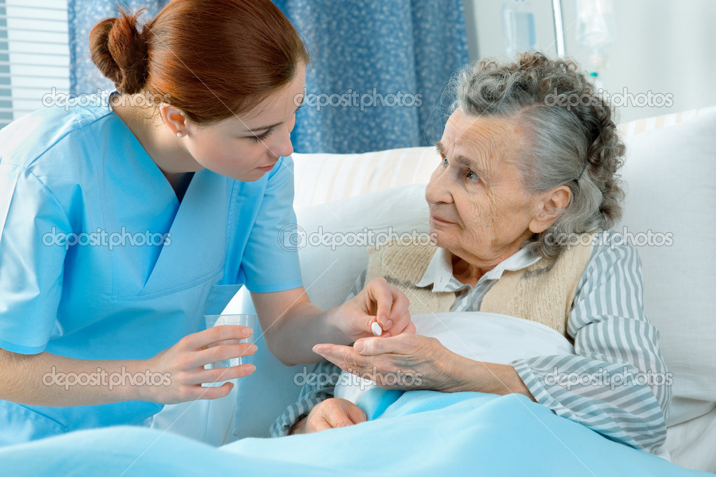 Nurse cares for a elderly woman lying in bed  — Stock Photo #6868493
