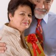 Elderly happy couple with gift — Stock Photo