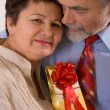 Elderly happy couple with gift — Stock Photo #6870214