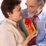 Elderly happy couple with gift — Stock Photo #6870218