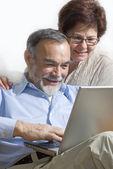 Starší pár, pomocí přenosného počítače — Stock fotografie