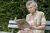 Old woman reading newspaper — Stock Photo