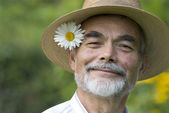 Senior with ox-eye daisy — Stock Photo