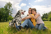 Loving couple with a Dalmatian outdoors — Stock Photo