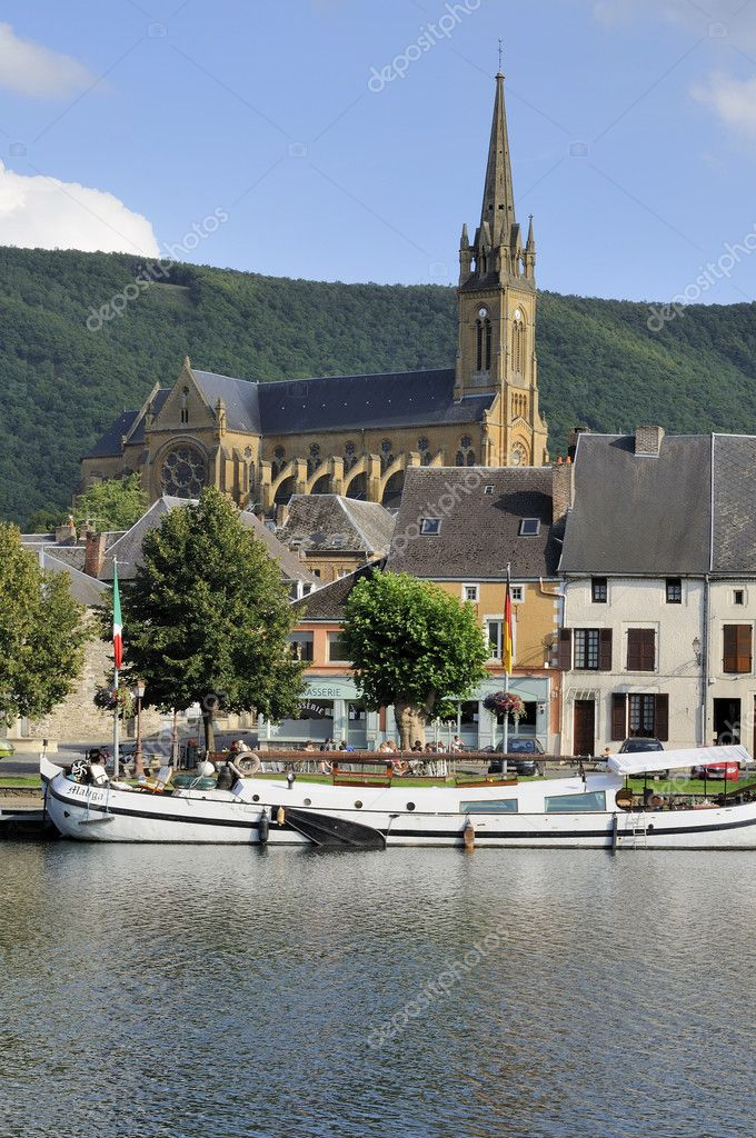 Foreshortening of boat and old houses on river embankment with touristic mooring, in background big church shot in bright summer light — Stock Photo #6941012