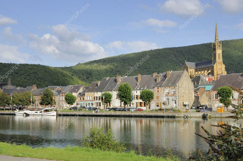 Foreshortening of river embankment with touristic mooring, in background old houses and big church, shot in bright summer light — Stock Photo #6941028