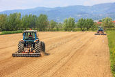 Two tractors farming in field — Stock Photo