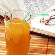 Multifruit juice with book and glasses — Stock Photo