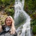 Smiling woman at waterfall — Stock Photo