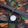 Stock Photo: Tubular compass and knife on camo