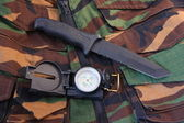 Tubular compass and knife on camo — Stock Photo