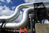 Industrial pipelines on pipe-bridge against blue sky — Stock Photo