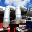 Industrial piping against blue sky - Stock Photo